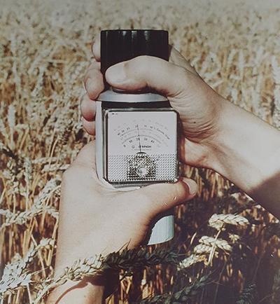 Vanha Wile-mittari pellolla maanviljelijän kädessä maanviljelijän kädessä